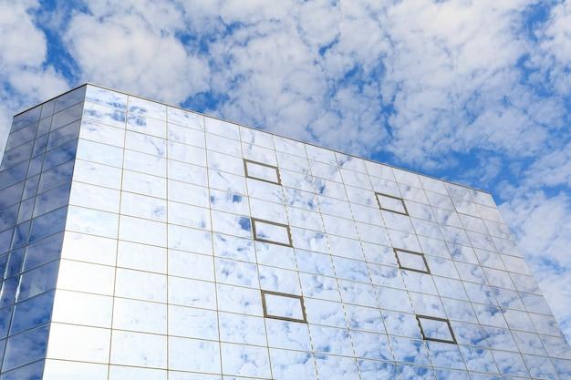 Wolken weerspiegeld in de glazen ramen van een modern gebouw