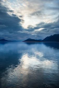 Wolken worden weerspiegeld in water in de fjorden van alaska.