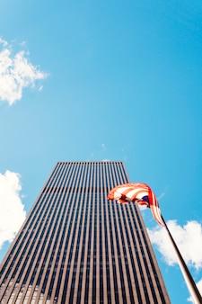 Wolkenkrabber in new york opgericht in de buurt van de vlag van de vs.