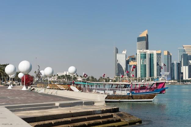 Wolkenkrabbers in het stadscentrum met water en bootvoorgrond van doha, qatar.