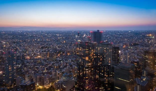Wolkenkrabbers in shibuya lichten op bij zonsondergang.