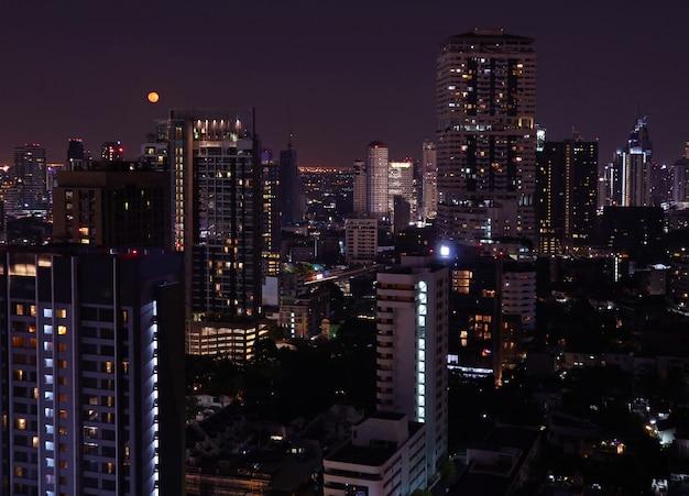 Wolkenkrabbersmening van bangkok de stad in op de heldere volle maannacht