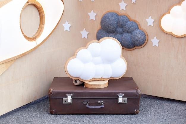 Wolkenlamp op koffer van houten muur met sterren. moderne woninginrichting. decoratieve wolk met lamp. wolkvormige led-lamp. interieur van ruimte voor kind, kleuterschool. verjaardag decoratie