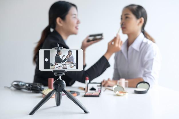 Woman blogger toont de huidige cosmetische cosmeticaproducten en zendt live streaming video uit