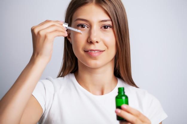 Woman face skin cosmetics, mooie vrouw houdt in de hand gezichtscrème