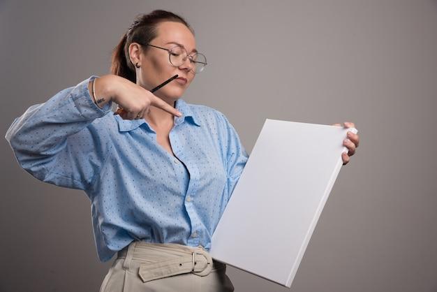 Woman wijzend op leeg canvas en penseel op grijze achtergrond