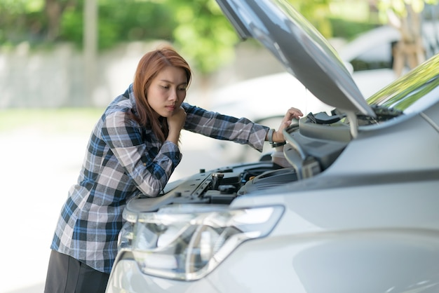 Womanchecking oliepeil in een auto, olie auto verversen