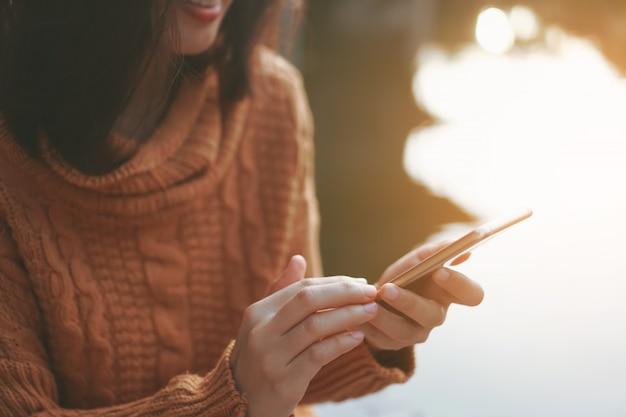 Womanhand die smartphone gebruiken om het werkzaken, sociaal netwerk, mededeling in openbare het werkruimte van het koffie te doen