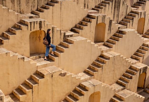 Womanm die op stepwells van chand baori in jaipur india lopen.