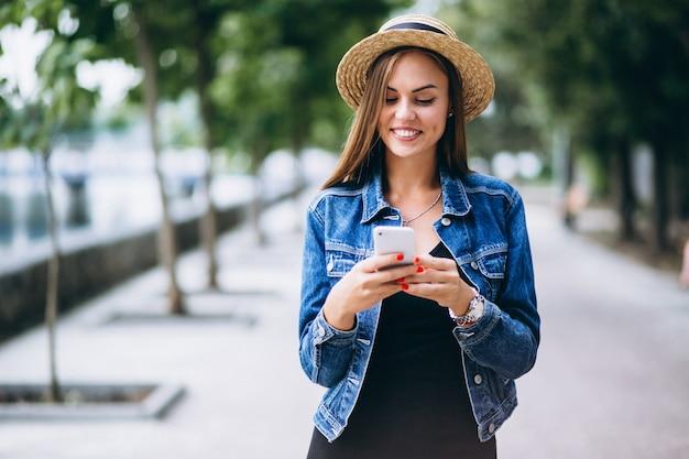 Womanwearing jurk en hoed buiten in park met telefoon
