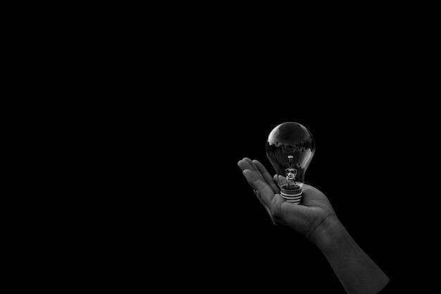 Women's houdt gloeilamp in het donker. - nieuw idee en innovatieconcept.