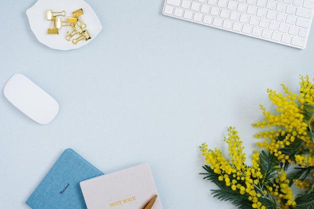 Womens desktop close-up van toetsenbord, notebooks, muis en gele bloemen op lichtblauwe achtergrond