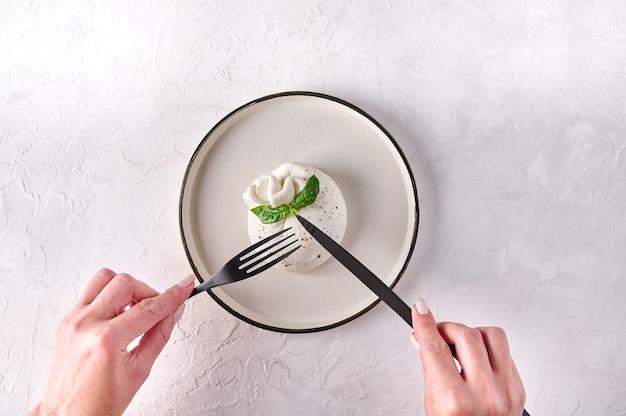 Womens handen gesneden met zwarte mes en vork burrata kaas met basilicum op lichte plaat bovenaanzicht kopie