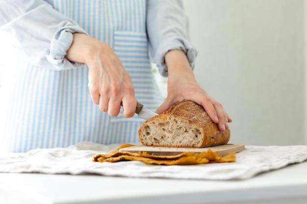 Womens handen houden brood tegen de achtergrond van een lichte schort