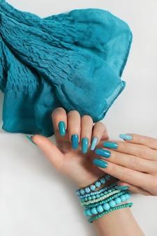 Womens handen op een lichte ondergrond met een blauwe manicure en sjaal