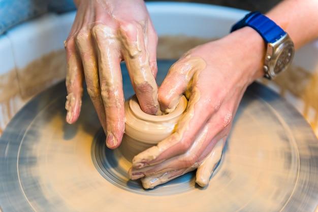 Womens handen van een pottenbakker die een aarden pot maakt