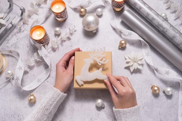 Womens handen versieren kerstcadeaudoos met witte decoraties wintervakantie concept