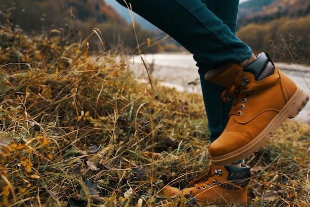 Womens voeten jeans schoenen droog gras herfst rivier bergen in de verte