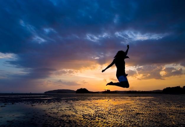 Womnan jumping bij zonsondergang in de zee