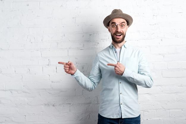 Wonder man in casual kleding, hoed en bril tegen een witte bakstenen muur staan en naar links wijzen door beide handen. copyspace