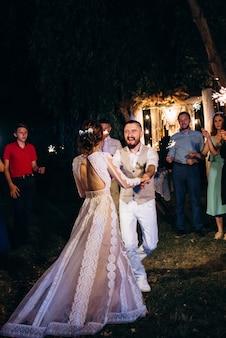 Wonderkaarsen op de bruiloft van de pasgetrouwden in de handen van vrolijke gasten