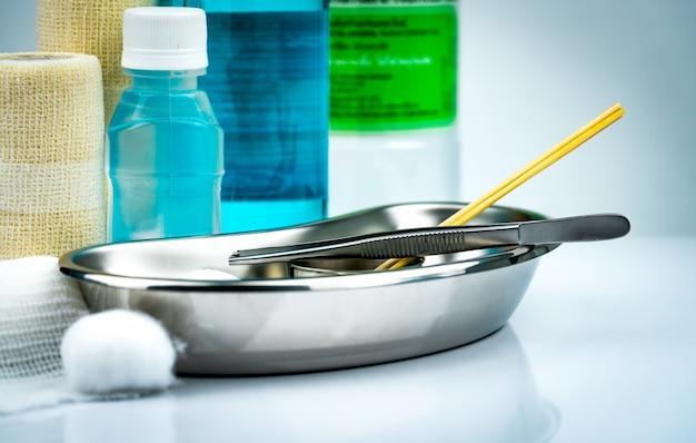 Wondverzorgingsset en roestvrijstalen plaat, tang, alcoholfles, samenhangend elastisch verband, wattenbolletje, container voor chirurgische ingrepen.