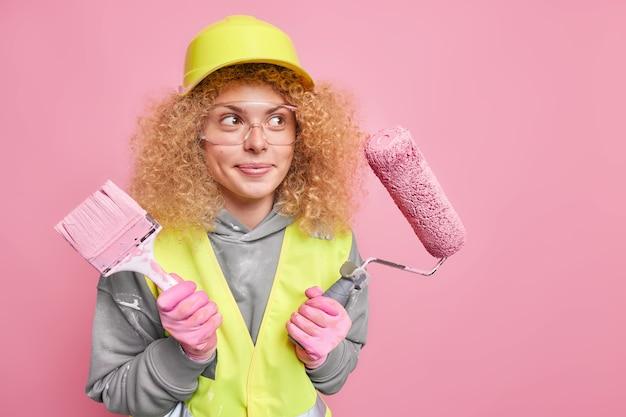 Woningbouw en reparatieservice. doordachte professionele vrouw constructeur met krullend borstelig haar draagt veiligheidshelm en transparante bril veiligheidshelm handschoenen uniform poses tegen roze muur