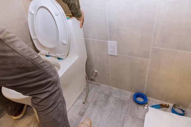 Woningbouw met nieuw wit toilet in badkuip een loodgieter renovatie badkamerhuis