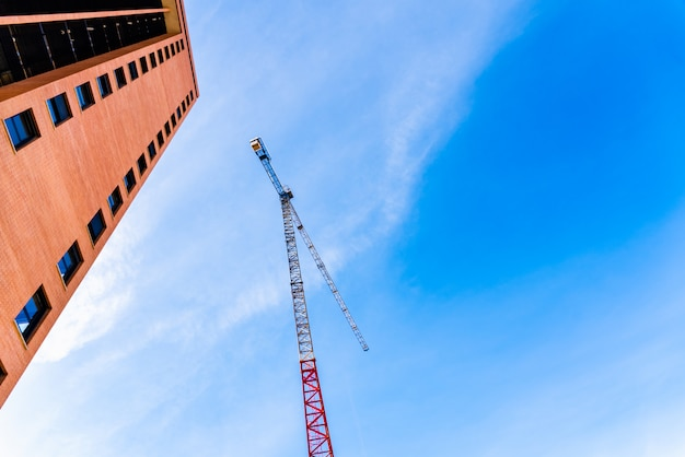 Woningbouwbedrijven installeren grote kranen om huizen te maken en worden door experts in de echte staat verkocht.