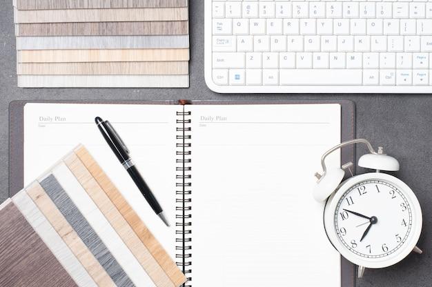 Woningrenovatieplanning met houtmonsters, toetsenbordnotitieboekje, pen en wekker