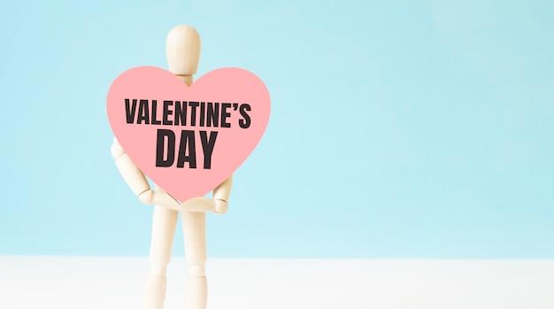 Wood man holding hart op blauwe achtergrond. tekst valentijnsdag. teken symbool idee, concept van liefde