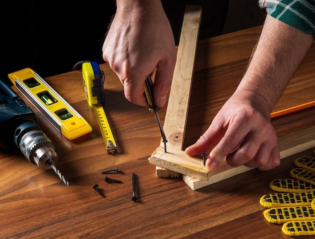 Woodworker verbindt de houten planken met een schroevendraaier en een schroef.