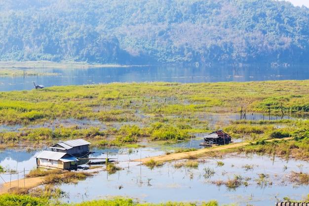 Woonboot in de songgaria-rivier en dichtbij berg in platteland van dorp in snagklaburi, thailand