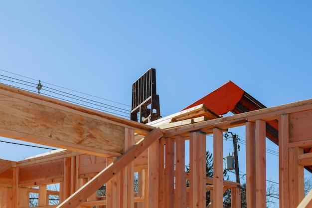 Woonbouwhuis, houten stralen met blauwe hemel bij bouw