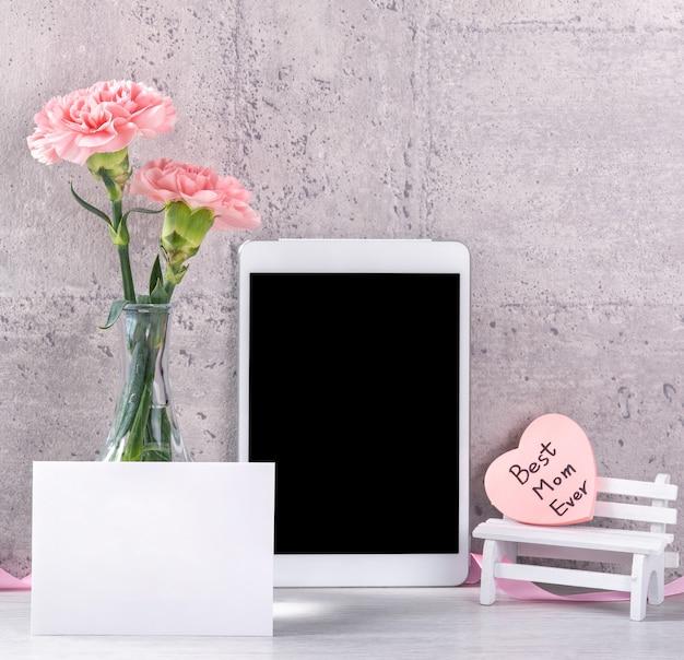 Woondecoratie met bloeiende anjer en tablet als fotolijst naast muur op tafel