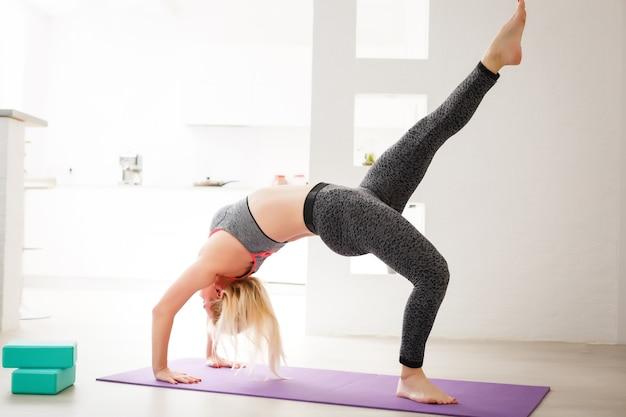 Woonkamer fitness workout meisje doet oefeningen thuis. jonge vrouw die spieren traint, gezonde levensstijl zonder naar de sportschool te gaan.