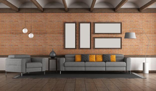 Woonkamer met bakstenen muur. grijze bank en fauteuil en gewelfd plafond