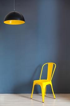 Woonkamer met blauwe stoel en zwarte lamp