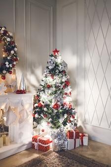 Woonkamer met kerstboom versierd met speelgoed en slingers