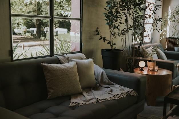 Woonkamer met sofa, kaarsen, ronde lamp, bloemen en planten