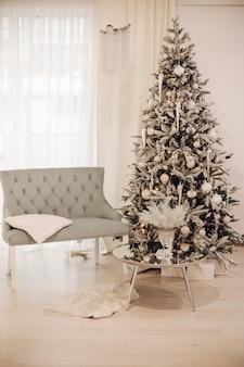 Woonkamer met tafel, bank en een boom waar speelgoed en ballen aan hangen