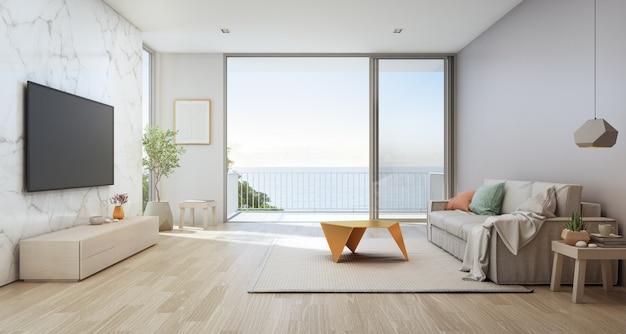 Woonkamer met zeezicht van luxe strandhuis met glazen deur en houten terras.