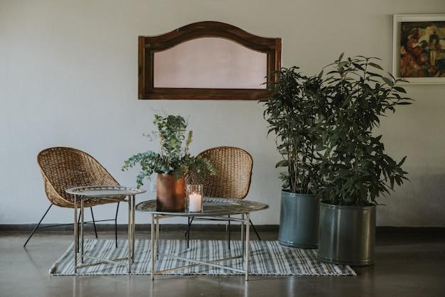 Woonkamer voor gasten versierd met bloemen, kaarsen en moderne stoelen