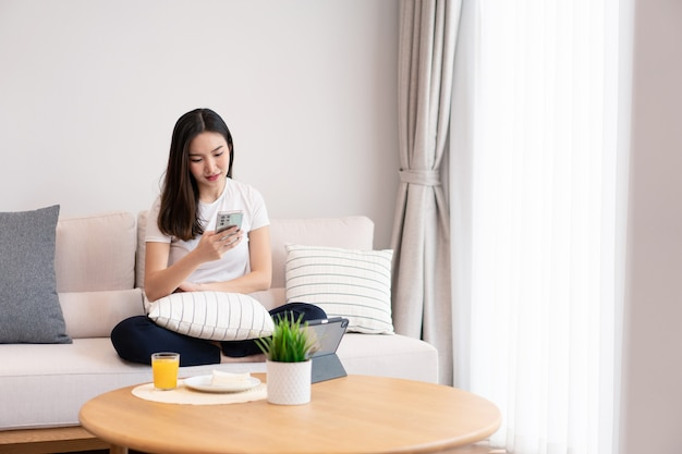 Woonkamerconcept een langharig meisje dat tijd doorbrengt op de elektronische apparaten in de gezellige kamer.