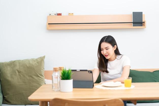 Woonkamerconcept een meisje met lang haar dat in de woonkamer zit te surfen op internet met haar smartphone.