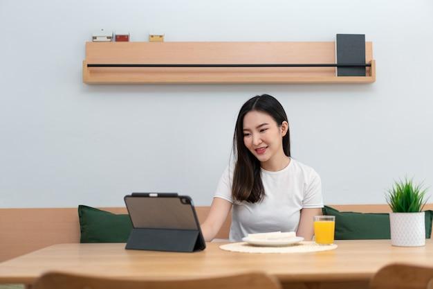 Woonkamerconcept een vrouw die haar elektronische apparaat gebruikt om op afstand te werken in de gezellige kamer van de coffeeshop.