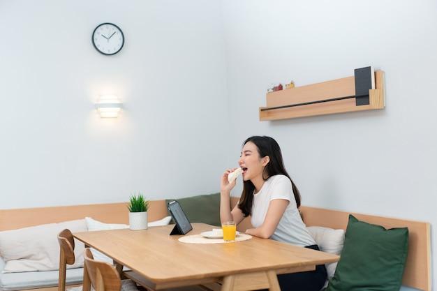 Woonkamerconcept een vrouwelijke volwassene die geniet van het eten van sandwiches en sinaasappelsap die naar online media kijkt in de werkpauze.