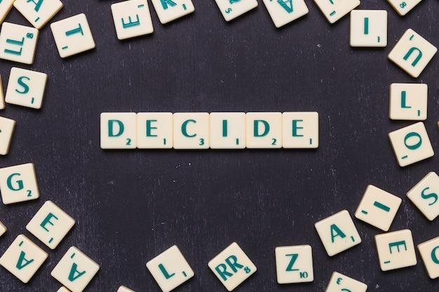 Woord beslissen scrabble letters over zwarte achtergrond