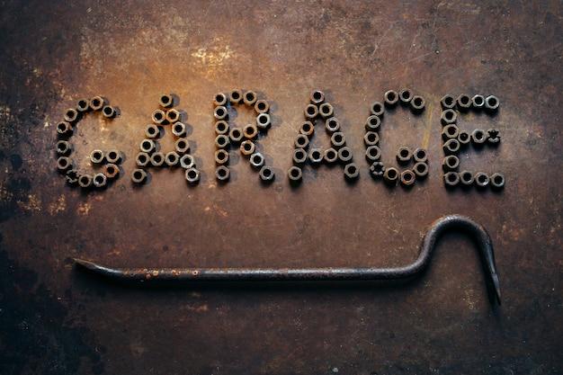 Woord garage gemaakt van noten koevoet op roestig metalen bureau