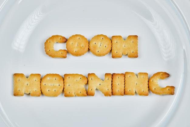 Woord goedemorgen gespeld met crackers op een witte plaat.